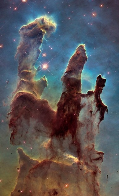NASA's Hubble Space Telescope has revisited the famous Pillars of Creation, revealing a sharper and wider view of the structures in this visible-light image. Astronomers combined several Hubble exposures to assemble the wider view. The towering pillars are about 5 light-years tall. The dark, finger-like feature at bottom right may be a smaller version of the giant pillars. The new image was taken with Hubble's versatile and sharp-eyed Wide Field Camera 3. The pillars are bathed in the blistering ultraviolet light from a grouping of young, massive stars located off the top of the image. Streamers of gas can be seen bleeding off the pillars as the intense radiation heats and evaporates it into space. Denser regions of the pillars are shadowing material beneath them from the powerful radiation. Stars are being born deep inside the pillars, which are made of cold hydrogen gas laced with dust. The pillars are part of a small region of the Eagle Nebula, a vast star-forming region 6,500 light-years from Earth. The colors in the image highlight emission from several chemical elements. Oxygen emission is blue, sulfur is orange, and hydrogen and nitrogen are green. Object Names: M16, Eagle Nebula, NGC 6611 Image Type: Astronomical Credit: NASA, ESA, and the Hubble Heritage Team (STScI/AURA)
